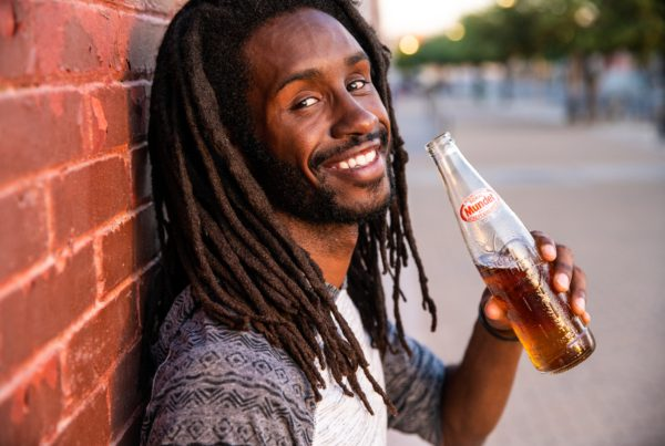 Smiling man sips on low-alcohol beer drink.